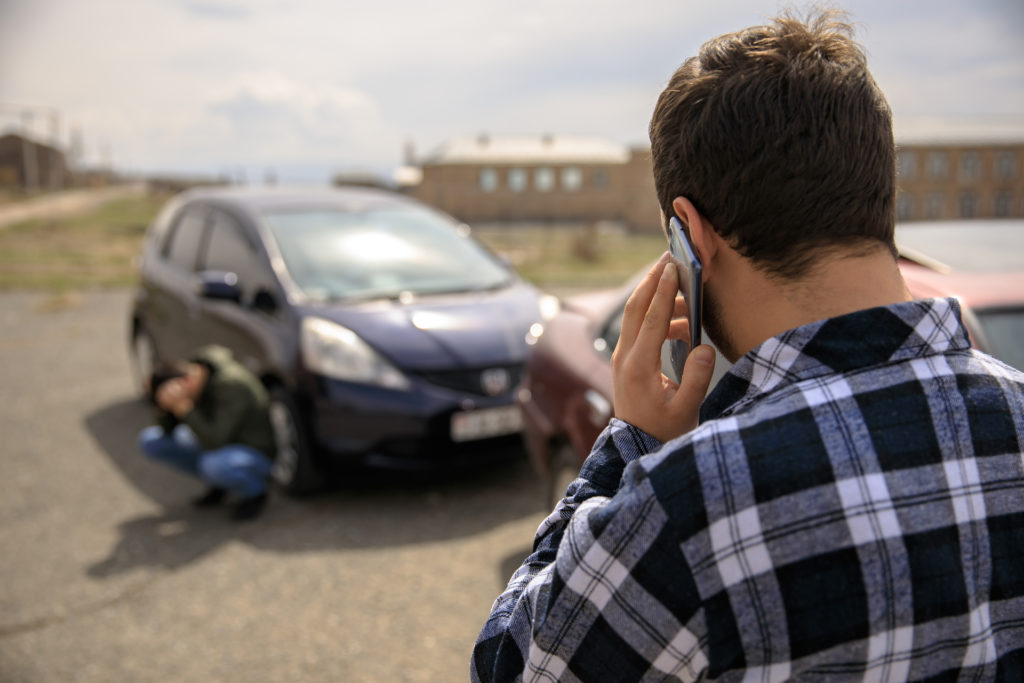 Man calling lawyers after car wreck.