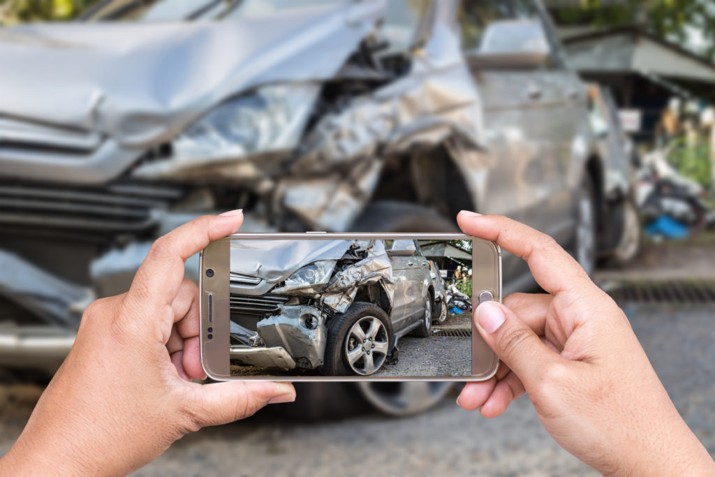 A phone taking a picture of a car after a wreck
