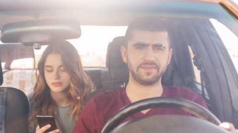 A male driver transporting a female passenger in a rideshare.