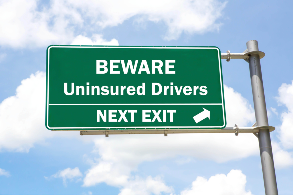 Green overhead road sign with a Beware of Uninsured Drivers Next Exit concept against a partly cloudy sky background.
